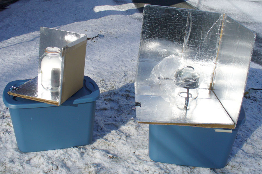 image of two solar cookers in the snow on a sunny day midwinter.